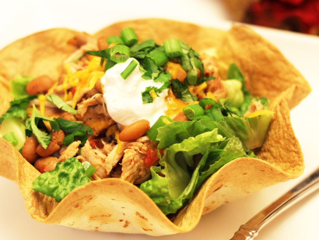 Remove chicken from the crock pot. Using two forks shred the chicken and place back in the crock pot along with pinto beans, lime juice and fresh cilantro. Cover and cook on HIGH an additional 30 minutes. Optional: garnish with greek yogurt and fresh cilantro. Serve.